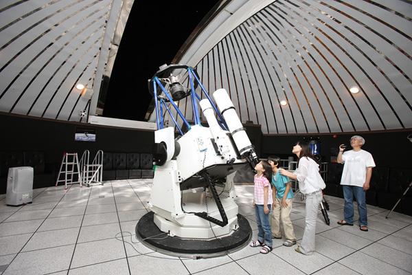 천문과학관 주망원경을 통해 천체관측을 하고 있는 가족.