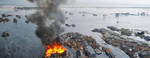 동일본 대지진이 강타한 지난달 11일 쓰나미로 물바다가 된 일본 미야기현 센다이의 한 마을에서 집들이 시커먼 연기를 내뿜으며 불타고 있다. 현재까지 지진과 쓰나미로 일본이 입은 경제적 피해는 최대 25조엔(GDP의 5%)으로 집계된다. /AP연합뉴스