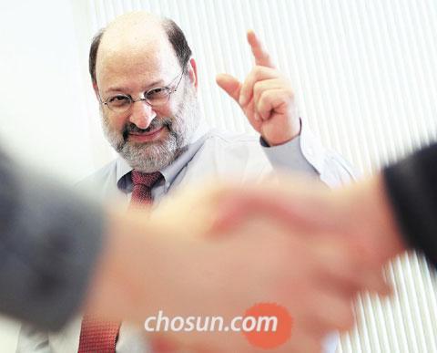 """'협상의 대가' 스튜어트 다이아몬드 와튼스쿨 교수가 두 남자가 악수를 나누는 모습을 바라보며 '바로 이거야' 하는 표정을 짓고 있다. 그는 """"힘과 논리 대신 감성으로 상대방을 이해하면 더 많은 것을 얻어낼 수 있다""""고 말했다. / 이태경 기자 ecaro@chosun.com"""