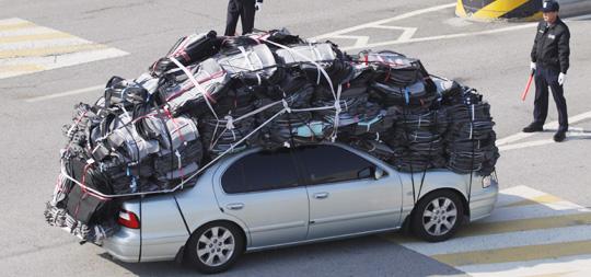 물건을 차량 지붕과 트렁크, 보닛 위에까지 잔뜩 실은 승용차