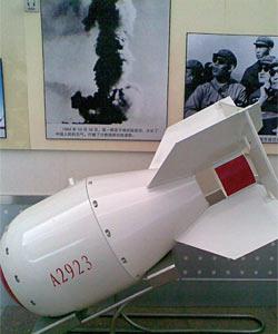 1964년 10월 16일 중국 신장위구르자치구 뤄부포에서 핵실험에 성공한 중국의 첫 번째 핵폭탄 실제 크기 모형. 뒤에 있는 사진은 핵실험 성공 후 피어오른 버섯구름.