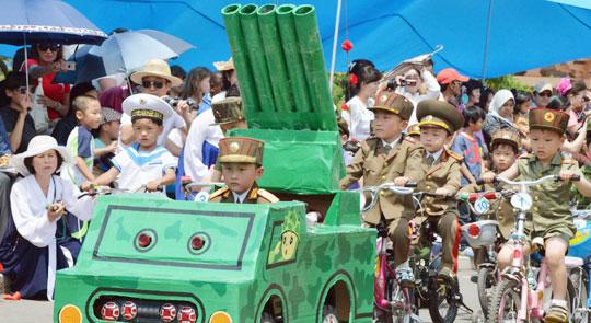 북한 어린이들이 1일 사회주의권의 어린이날에 해당하는'국제아동절'을맞아 평양의 만경대유희장에서 군복 차림으로 장난감 이동식 미사일 차량과 자전거를 타고 모의'군사 퍼레이드'를 하고 있다.