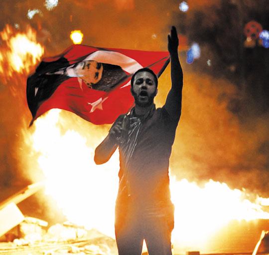 터키 수도 앙카라에서 2일 시위대가'터키 건국의 아버지'로 불리는 무스타파 케말 아타튀르크 초대 대통령의 사진이 인쇄된 국기를 들고 반(反)정부 구호를 외치고 있다.