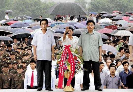비 안맞게 하려… 사람보다 더 중요한 김일성 弔花… 8일 평양에서 열린 김일성 사망 19주기 추모식에서 북한의 한 청년이 조화(弔花)가 젖지 않도록 우산을 씌워주고 있다