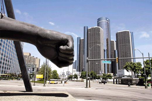 미 디트로이트에 전시된 주먹을 꽉 쥔 팔 모양의 조각상이 뒤에 보이는 미국의 자동차 제조업체인 GM 본사 건물을 향해 마치 강펀치를 날리는 듯하다. /조선일보DB