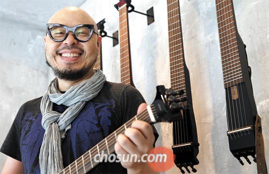 """기타리스트 이병우(48)가 서울 삼성동에 있는 자신의 기타 가게에서 직접 제작한 '기타 바(Guitar Bar)'를 들고 있다. 이씨는 """"스페셜올림픽과 뮤직페스티벌 일을 하면서 제 자신이 배우는 게 참 많다""""고 했다"""