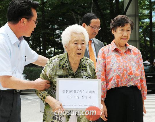 13일 오전 일본군위안부 피해자 이옥선(85·왼쪽)·강일출(85·오른쪽) 할머니가 위안부 피해자 12명을 대표해'일본군위안부 피해자 민사조정 신청서'를  제출하기 위해 서울 서초동 서울중앙지법에 들어서고 있다.