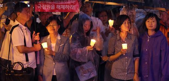 지난 31일 서울역 광장에서 열린'국정원 대선 개입 규탄 10차 범국민 촛불 집회'에 통합진보당 김재연(오른쪽 둘째) 의원 등이 참석해 빗속에 촛불을 들고 있다. 이날 집회 참석자들은'불법 당선 박근혜 하야''내란 음모 조작 국정원을 해체하라'고 주장했다.