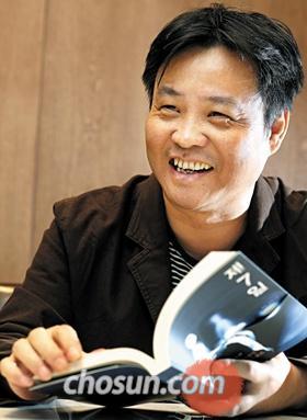 중국 작가 위화가 26일 인천공항에서 자신의 책 '제7일'의 한국어판을 보며 웃고 있다.