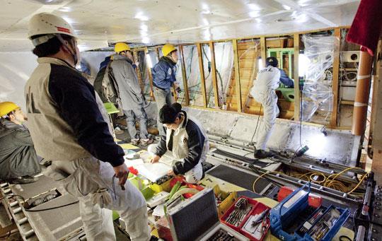 일본 국립환경연구소와 일본항공 담당자들이 이 항공사 비행기 동체 화물실에 이산화탄소 측정기를 설치하고 있다.