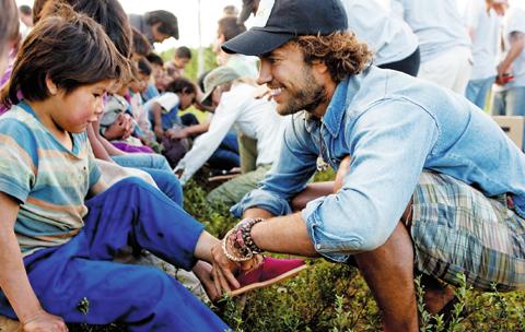 """마이코스키 탐스슈즈 창업자가 아르헨티나를 방문해 가난한 어린이들에게 신발을 신겨주고 있다. 그는 """"신발을 기부받은 아이들은 인생에 자부심과 믿음을 갖게 된다""""고 말했다."""