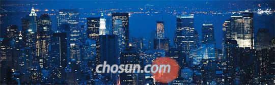 """미국 뉴욕 엠파이어스테이트 빌딩에서 바라본 월스트리트 야경. 로버트 쉴러는 """"금융에는 빈틈이 존재하지만 더 풍요롭고 평등한 사회를 건설하도록 도울 잠재력도 갖고 있다""""고 말한다"""