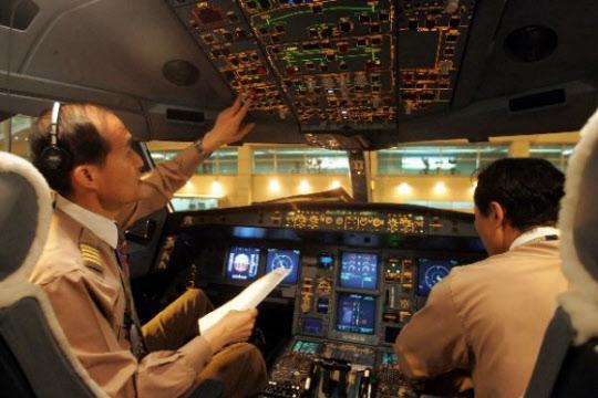 중국 등 해외 항공사들과 저가항공업계의 성장으로 국내 조종인력에 대한 수요가 크게 늘고 있다. 사진은 이륙 전 기내 상황을 점검 중인 아시아나항공 파일럿들. /조선일보 DB