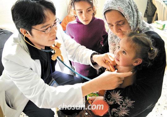 열린의사회 의료봉사자 이원웅(왼쪽) 응급의학과 전문의가 시리아 난민 여아를 진료하고 있다.