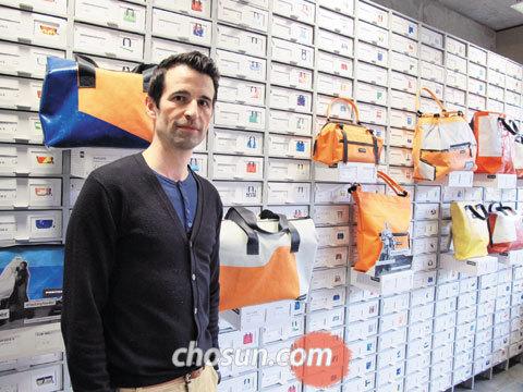 프라이탁의 창업자이자 크리에이티브 디렉터인 마르쿠스 프라이탁씨가 본사 직영매장의 진열장 앞에서 제품을 설명하고 있다.