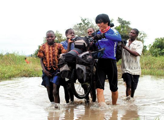자전거로 세계 여행을 다닌 문종성씨는 지난 2010년 여름 아프리카 모잠비크 북부 니아사 국립공원 인근 산악 지역을 지나다 길을 잃었다. 사진은 문씨가 현지 원주민들의 도움을 받아 폭이 약 30m 정도인 물웅덩이를 건너는 모습이다.