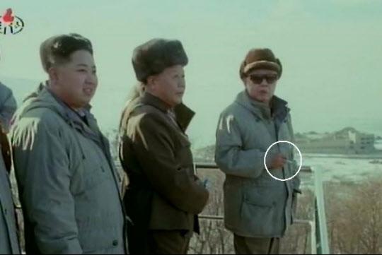 조선중앙TV가 2012년 1월 8일 방영한 기록영화에서 북한 김정일(오른쪽)이 김정은(제일 왼쪽)과 함께 군사훈련 참관도중 담배(동그라미 안)를 손에 쥐고 있는 장면이 공개됐다. 김정일은 2008년 뇌졸중으로 쓰러진 뒤에도 담배를 계속 피웠던 것으로 알려졌다.