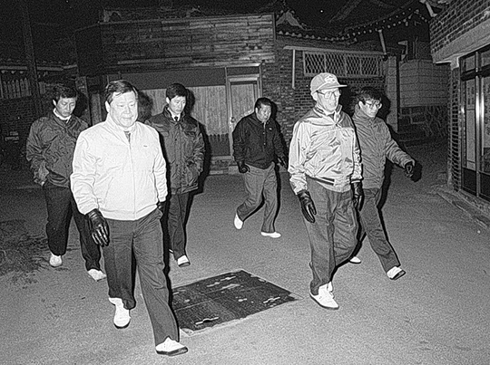 정주영 현대그룹 회장이 이른 새벽 아들들과 함께 삼청동 자택에서 계동 사옥으로 도보로 출근하고 있다. 왼쪽에 몽구씨와 오른쪽에 몽헌씨가 호위하고 있다. 1988년 1월 6일/조선일보DB