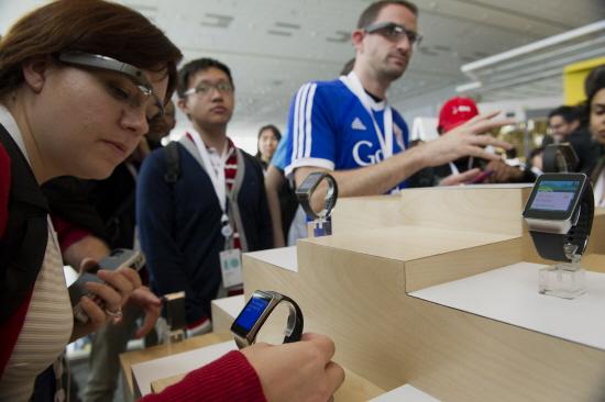 25일 열린 I/O 개발자 컨퍼런스 참가자들이 구글글라스와 삼성전자의 기어라이브를 시현해보고 있다. /사진=블룸버그