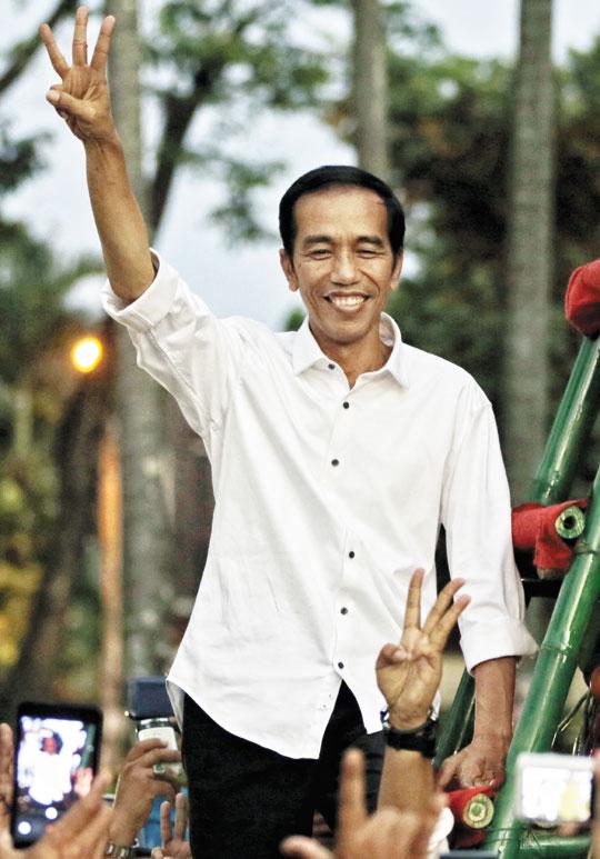 조코 위도도 인도네시아 대통령 당선자가 23일 수도 자카르타에서 지지자들을 향해 정치 통합을 의미하는 손가락 세개를 펴 보이고 있다.