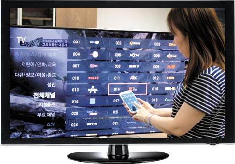 '티빙스틱'을 TV에 연결한 뒤 스마트폰으로 채널을 선택하고 있다.