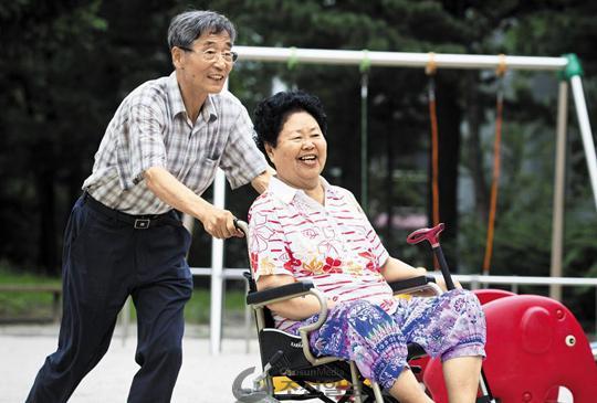 """지난달 6일 경기도 구리시 한 아파트 단지에서 문기홍 할아버지가 뇌졸중을 앓는 아내 최순례 할머니와 산책을 즐기고 있다. 최 할머니는""""만날 싸워도 부부밖에 없다""""고 했다. /김지호 기자"""