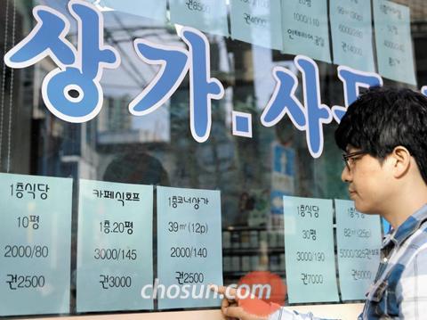 정부가'상가 권리금 보호 방안'을 발표한 24일, 서울 송파구 신천역 인근 부동산 중개업소에 내걸린 상가 매물표를 지나가던 시민이 유심히 쳐다보고 있다.
