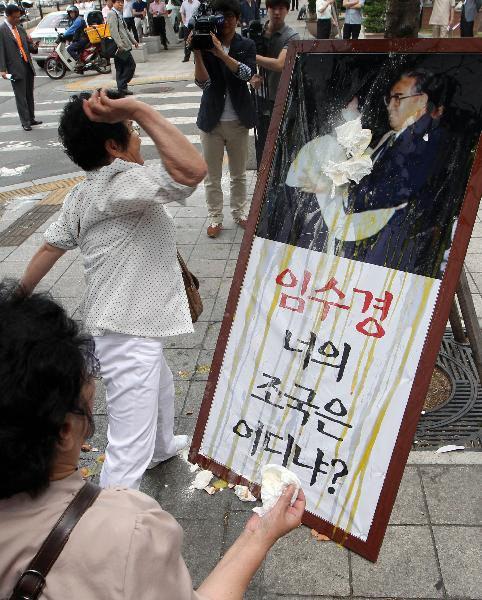 2012년 6월 11일 오전 서울 여의도 국회 앞에서 탈북단체 회원들이 기자회견을 열고 탈북자비하발언을 한 민주통합당 임수경 의원과 최재성 의원을 규탄하며 임수경 의원이 지난 1989년 무단 방북한 뒤 김일성을 만나 포옹하는 사진에 계란과 밀가루를 던지고 있다.
