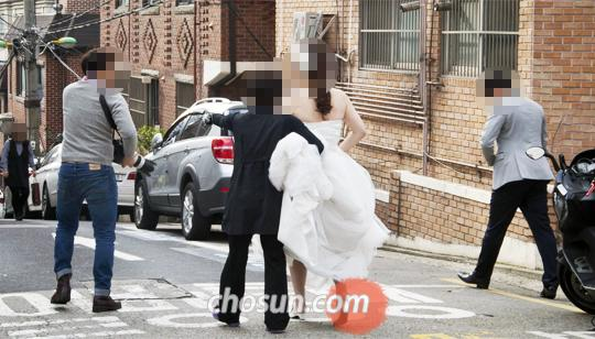 웨딩드레스 가게·스튜디오 등이 밀집한 서울 강남구 청담동의 한 거리에서 한 쌍의 신랑 신부가 턱시도와 웨딩드레스를 차려입고 사진 촬영을 하기 위해 이동하고 있다