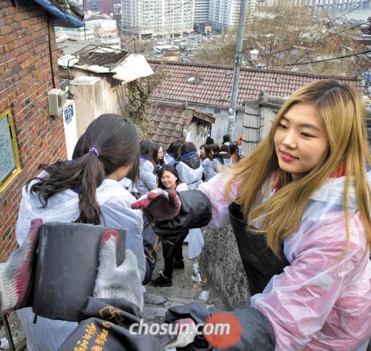 성탄절을 이틀 앞둔 지난 23일 오후 숙명여대 학생들이 서울 한남동 쪽방촌 골목길에 줄을 서서 연탄을 나르고 있다.