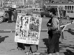 1962년 12월 서울역 앞 지게꾼 옆을 걸어가는 샌드위치맨.