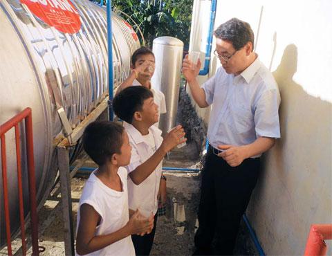 지난 2월 필리핀 일로일로 섬의 한 마을을 찾은 김용주 한국환경산업기술원장이 아이들과 빗물을 정수해 만든'깨끗한 물'을 마시고 있다. 한국환경산업기술원은 국내 환경 기술을 활용해 하루 60)의 빗물을 정수할 수 있는 설비를 주민들에게 설치해줬다.