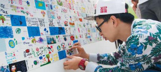 지난 10일 개최된'아트업 페스티벌'에 참여한 팝아티스트 찰스장이 2000명의 시민과 함께한 공공아트 '해피 투게더(Happy together)'에 폐카드로 만든 그림을 붙이고 있다.