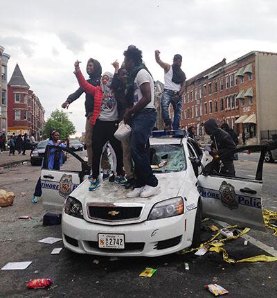 미국 메릴랜드 주 볼티모어에서 흑인 시위자들이 훼손된 경찰차 위에서 환호하는 모습./AP 뉴시스