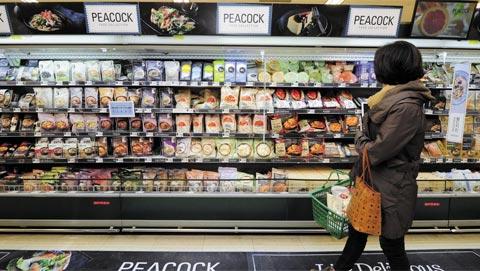 서울 용산에 있는 이마트 식품매장을 찾은 한 여성 고객이 가정 간편식으로 가득 채워진 진열대를 둘러보고 있다.