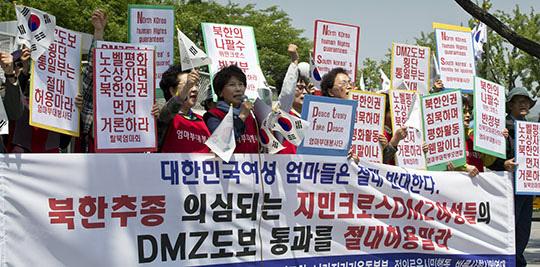 엄마부대봉사단 등 보수단체 회원들이 2015년 5월 13일 오전 서울 정부서울청사 정문 앞에서 기자회견을 갖고 위민크로스의 비무장지대(DMZ) 판문점 도보 통과를 불허할 것을 통일부에 요구하며 구호를 외치고 있다./조선일보DB