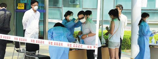 10일 전국 최초로 메르스 환자만을 진료하는'메르스 전담병원'으로 지정된 경기도립 수원병원 앞 임시 진료소에서 방문객들이 의료진의 문진을 받고 있다.