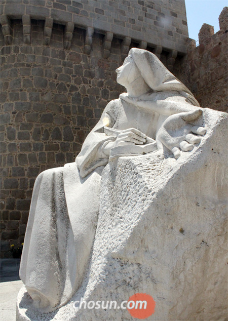 스페인의 아빌라 성벽 밖에 서 있는 대 데레사 성녀의 석상. 맨발 차림에 하느님을 바라보며 펜을 들고 영성 서적을 쓰고 있는 모습이다.