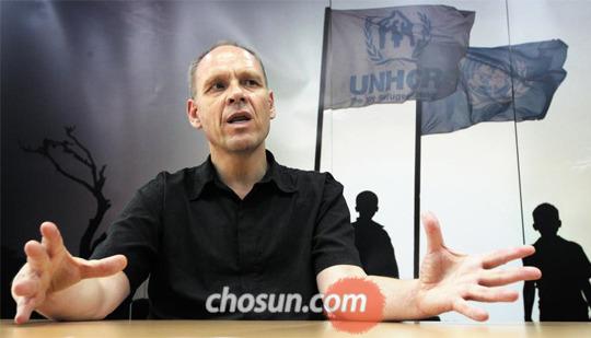 유엔난민기구 한국대표부 더크 헤베커 대표가 서울 중구 사무실에서 이야기하고 있다. 배경은 유엔난민기구가 세운 난민촌의 난민들 모습이다.