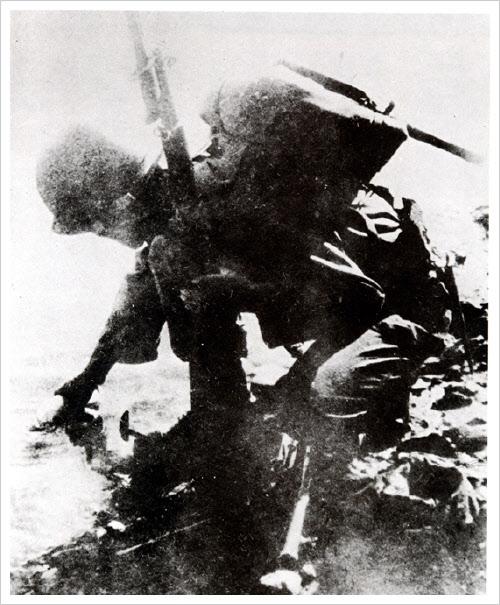 6사단 장병으로 보이는 국군이 압록강에 도착해 물을 뜨고 있는 장면이다.
