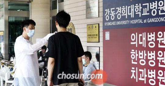 28일 서울 강동경희대병원에서 마스크를 쓴 병원 관계자가 방문자 체온을 재고 있다.