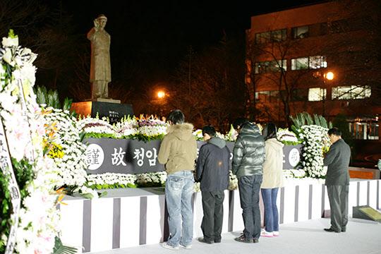 밤중에 '박태준 조각상'에 헌화 묵념하는 포스텍 학생들.