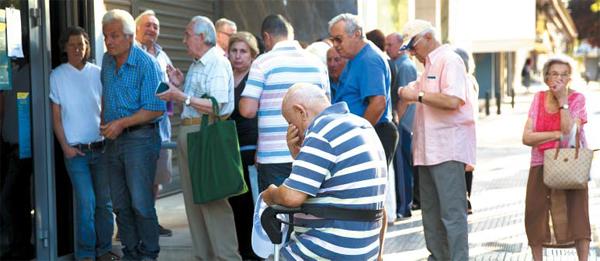 우울한 그리스 - 13일(현지 시각) 그리스 아테네 중심가에서 휠체어 탄 노인이 연금을 수령하기 위해 은행 앞에서 기다리고 있다. 이날 국제 채권단과 그리스 사이에 협상이 타결됨에 따라 그리스는 3차 구제금융을 받게 됐다. 그러나 은행 영업 재개까지는 수일이 걸릴 것으로 예상된다