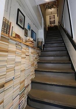 헌책방으로 오르는 계단. 벽면에는 헌책이 쌓여있고, 천장에는 책이 주렁주렁 매달려 있다. / 이진한 기자