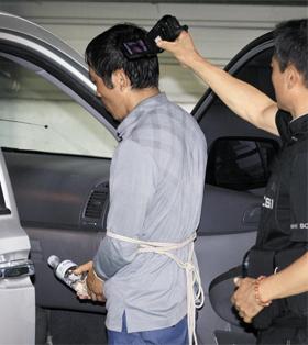 23일 오전 서울 성동구 한 빌라에서 진행된 '트렁크 시신 사건' 현장검증에서 피의자 김일곤이 범행 장면을 재연하고 있다.