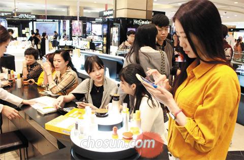 1일 서울 소공동 롯데백화점 본점 화장품 매장을 찾은 중국인이 스마트폰에 저장한 구매 물품 목록(目錄)을 확인하고 있다. 옆에 있는 중국인 관광객들은 스마트폰과 계산기를 손에 쥐고 할인 정보와 가격 등을 비교하고 있다.
