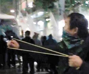 지난 14일 서울 도심에서 벌어진 폭력 시위에서 두건을 쓴 한 시위 참가자가 새총으로 경찰을 겨누고 있다.