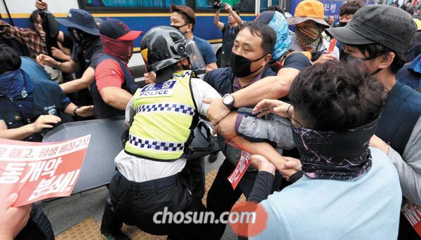 지난 9월 23일 오후 서울 중구 정동 민노총 사무실 앞에서 민노총 조합원들이 총파업 집회를 한 뒤 집회 신고를 하지 않은 구역으로 행진을 시도하다 이를 막는 경찰을 끌어내고 있다.
