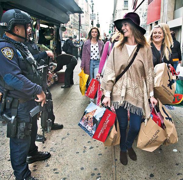테러 경계 경찰과 해맑은 쇼핑객 - 27일(현지 시각) 미국 뉴욕 헤럴드광장에서 양손에 쇼핑백을 가득 든 시민들이 경찰에게 웃어 보이고 있다. 미국은 파리 테러 이후 쇼핑센터 등 공공장소 경비를 강화하고 있다.