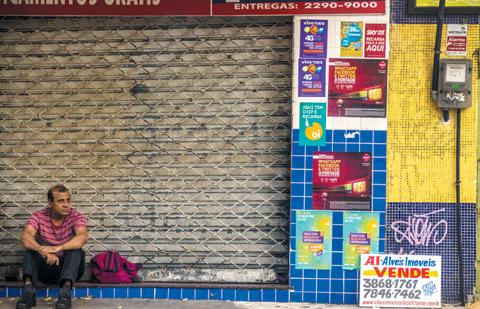 브라질 리우데자네이루의 문 닫힌 상점 앞에 한 남자가 앉아 있다.